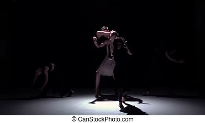 Graceful contemporary dance of five dancers on black, shadow, slow motion