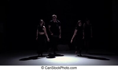 Graceful contemporary dance of four dancers on black, shadow, slow motion