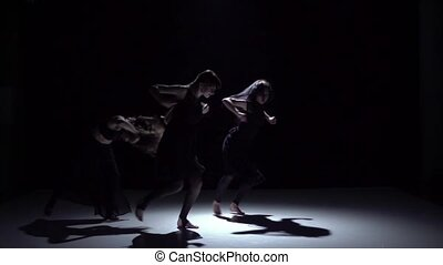 Graceful contemporary dance of three dancers on black, shadow, slow motion