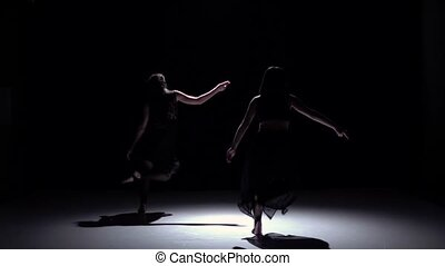 Graceful contemporary dance of two dancers on black, shadow, slow motion