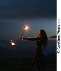 Graceful elegant red haired female fireshow performer