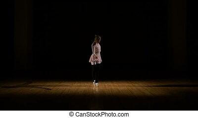 Graceful girl dancer practicing ballet at the studio