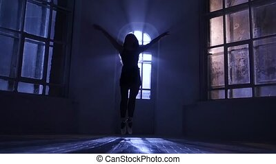 Graceful girl dancing contemporary dance, jumps in silhouette. Slow motion