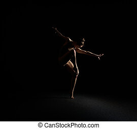 Graceful girl dancing emotionally in dark studio