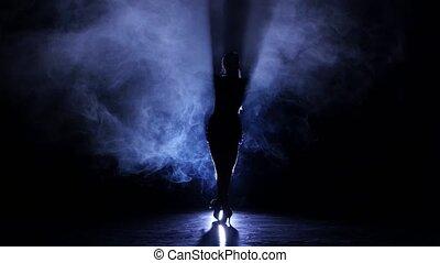 Graceful girl dancing in studio cha-cha-cha, silhouette. Dark background, blue backlight