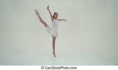 Graceful Girl Gymnast Performing Rhythmic Gymnastics Exercise, Sportive Girl Dancing Wearing Sport Dress, Beautiful Long Haired Teenager Posing in Studio Against White Background