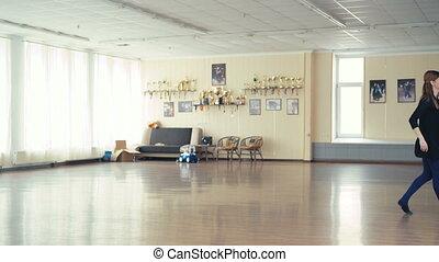Graceful girl practicing ballet in dance studio