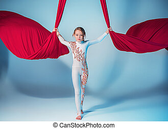 Graceful gymnast performing aerial exercise with red fabrics...