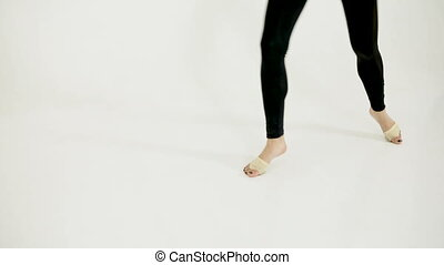 graceful legs of a ballerina dancing on a white floor