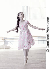 Graceful little girl dancing in ballet studio