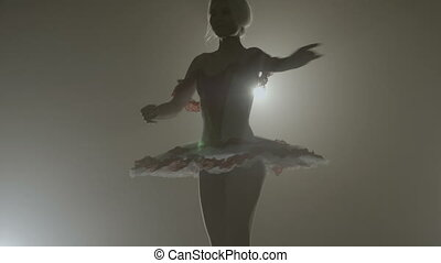 Graceful sensual ballerina wearing white outfit dancing and spinning elegantly in a dark background with spotlight