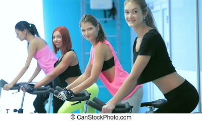 Graceful sexy girl pedaling and looking at the camera on a stationary bike