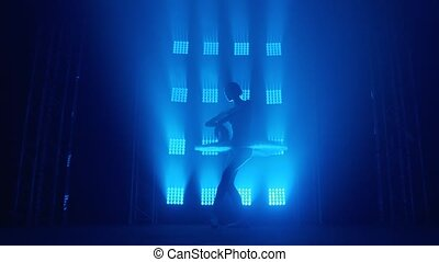 Graceful silhouette ballerina doing a workout in the classroom. Smoke in the rays of blue light. Ballet dancer in white tutu, girl in pointe, whirls around you, slow motion.