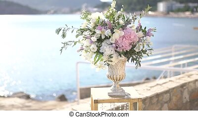 graceful vase with a bouquet of peonies, lisianthus, delphiniums and olive twigs, wedding venue decor. High quality FullHD footage