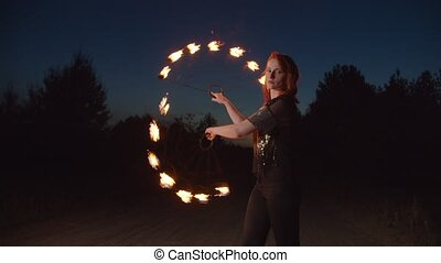 Graceful woman juggling with fire fans at night - Attractive...