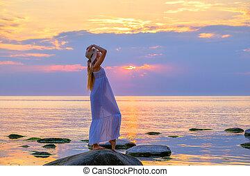 Graceful woman on seashore at sunset