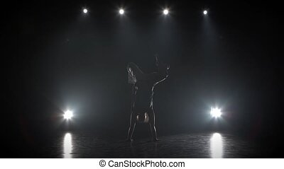Graceful woman practicing capoeira in darkness against...