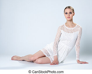 Graceful young girl posing in white lace dress