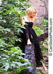 Gracious sensuality - Cute sexy woman in black dress sitting...