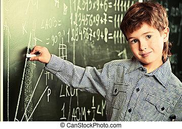 Portrait of a cute smiling schoolboy writing on a blackboard in a classroom.