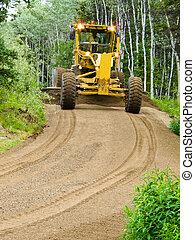 Grader resurfacing narrow rural road - Large yellow grader ...