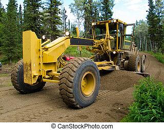 Grader resurfacing narrow rural road - Large yellow grader...