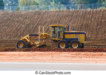 Grader - Road grader leveling hill for new highway, on...