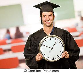graduado, homem, segurando, um, relógio de parede