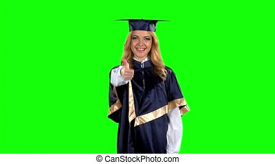 Graduate girl with a thumbs down. Green screen. Slow motion