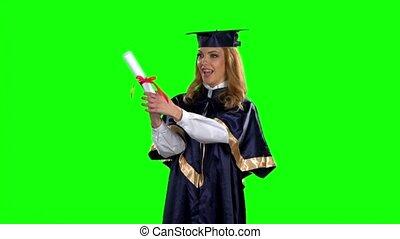 Graduate holding a diploma and kisses him. Green screen....