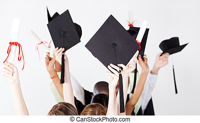 graduation caps and certificate - graduate holding...