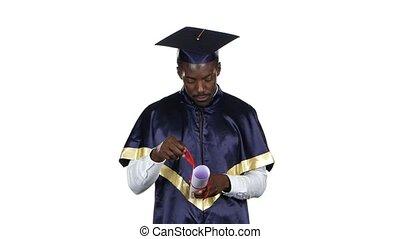 Graduate looks into the diploma. White - Graduate looks into...