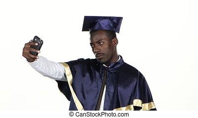 Graduate makes selfie photo. White. Close up