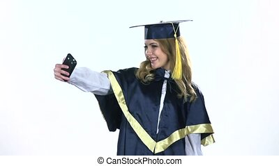 Graduate makes selfie photo. White. Slow motion
