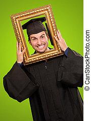 Graduate man looking through a frame