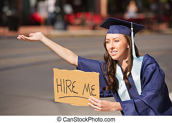 Graduate with Hire Me Sign - Single college graduate in gown...