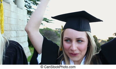 Graduated students raising their arms in front of the...
