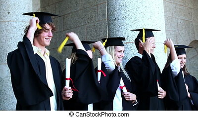 Graduates are passing he tassel from right to left together