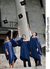 Graduates Hat Toss - A group of graduates toss their mortar...