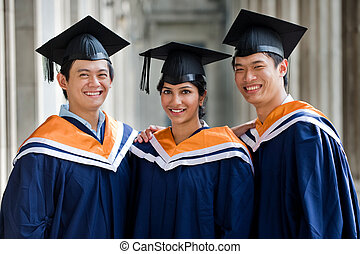 Graduates In Hallway - Three young graduates standing in a...