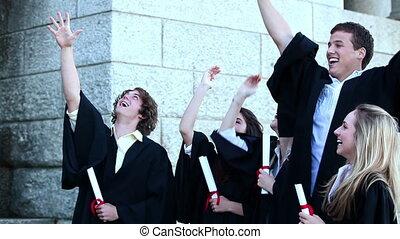 Graduates throwing mortar boards and dancing