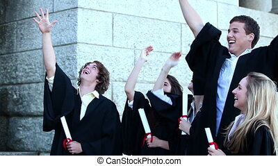 Graduates throwing mortar boards and dancing together