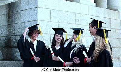 Graduates throwing mortar boards in the air while holding...