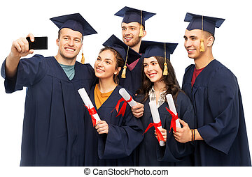 graduates with diplomas taking selfie by cellphone