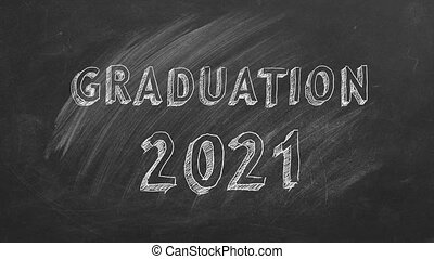 Hand drawing text GRADUATION 2021 on school blackboard