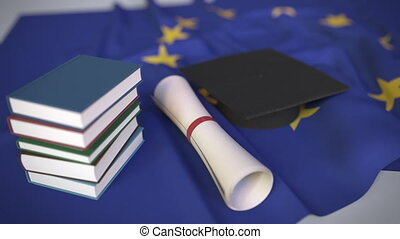 Graduation cap, books and diploma on the EU. Higher education in Europe related conceptual 3D animation