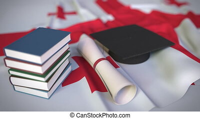 Graduation cap, books and diploma on the Georgian flag. Higher education in Georgia related conceptual 3D animation