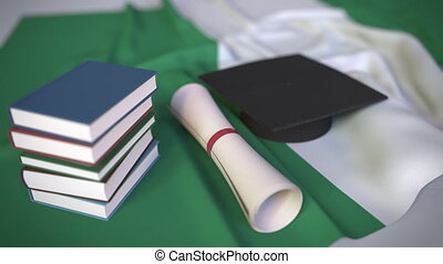 Graduation cap, books and diploma on the Nigerian flag. Higher education in Nigeria related conceptual 3D animation