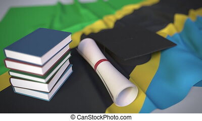 Graduation cap, books and diploma on the Tanzanian flag. Higher education in Tanzania related conceptual 3D animation