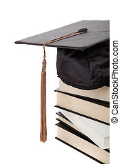 Graduation cap on top of a stack of books on white - a...